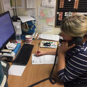 Surveyors' secretary making a booking